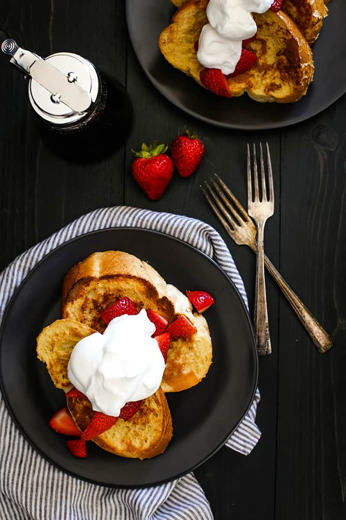 An overhead view of slices of Vanilla French Toast topped with strawberries and whipped cream.