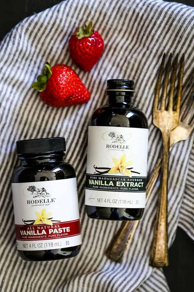 Jars of Rodelle Vanilla Paste and Vanilla Extract on a striped napkin.