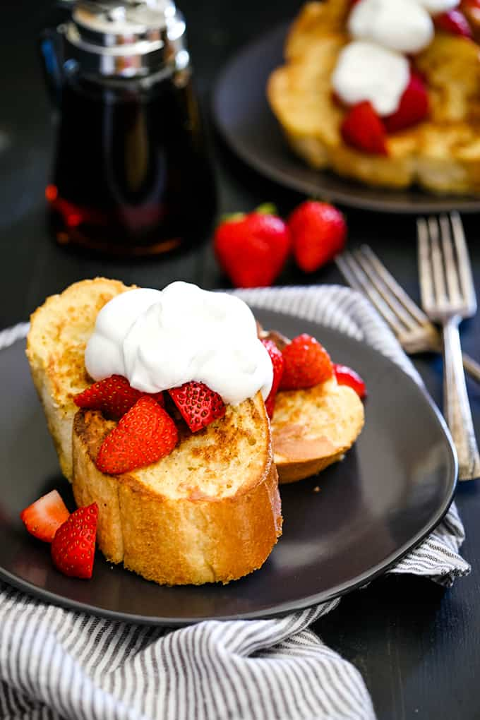 Slices of Vanilla French Toast on a plate on top of a striped napkin.