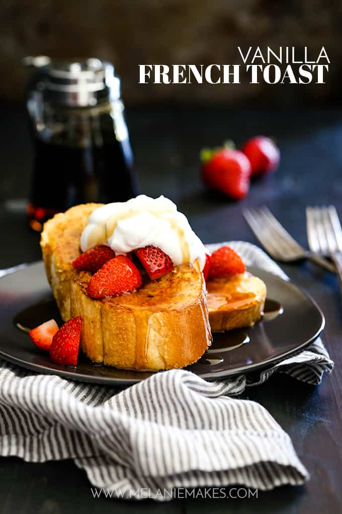 Two slices of Vanilla French Toast on a dark plate garnished with strawberries and whipped cream.