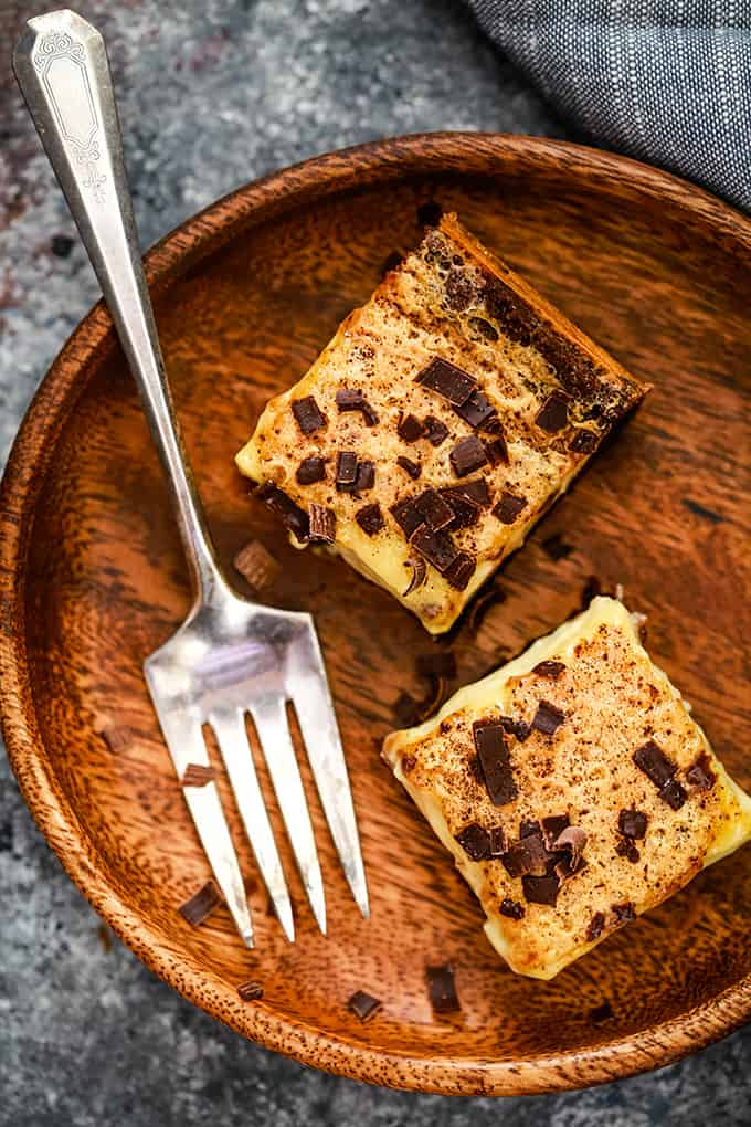 An overhead shot of two Chocolate Espresso Eggnog Bars sitting on a wooden plate with a fork.