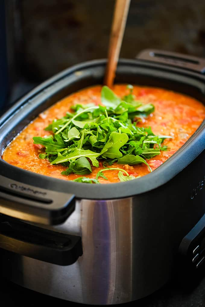A slow cooker of Slow Cooker Sausage Lentil and Arugula Soup on a dark background.