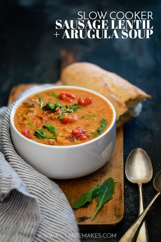 A white bowl of Slow Cooker Sausage Lentil and Arugula Soup sits on a wood cutting board next to a striped napkin, crusty bread and two spoons.