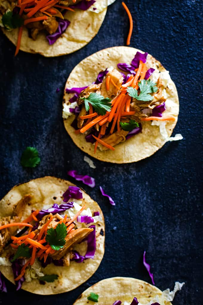 Four Slow Cooker Hoisin Chili Chicken Tacos rest on a dark surface.