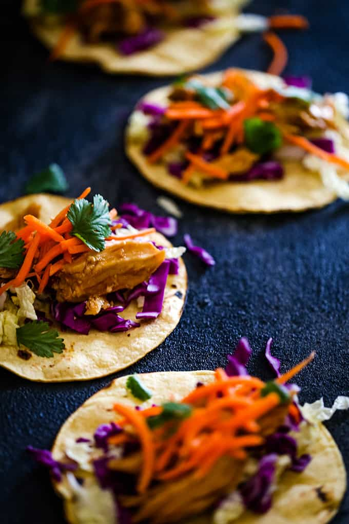 Slow Cooker Hoisin Chili Chicken Tacos are garnished with a crunch slaw and cilantro leaves.
