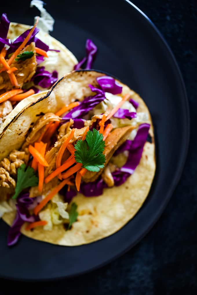 Slow Cooker Hoisin Chili Chicken Tacos topped with crunch slaw.