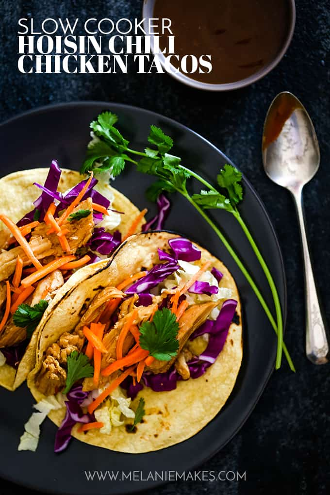 Two Slow Cooker Hoisin Chili Chicken Tacos sit on a black plate garnished with fresh cilantro.