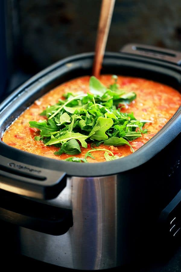 This Slow Cooker Sausage Lentil and Arugula Soup is easy.  BEYOND easy.  As in, if you can brown sausage and then literally toss every other ingredient in your slow cooker, you can consider dinner done.  D-O-N-E.  Sausage and lentils bespeckle a tomato soup base before being swirled together with peppery, fresh arugula.