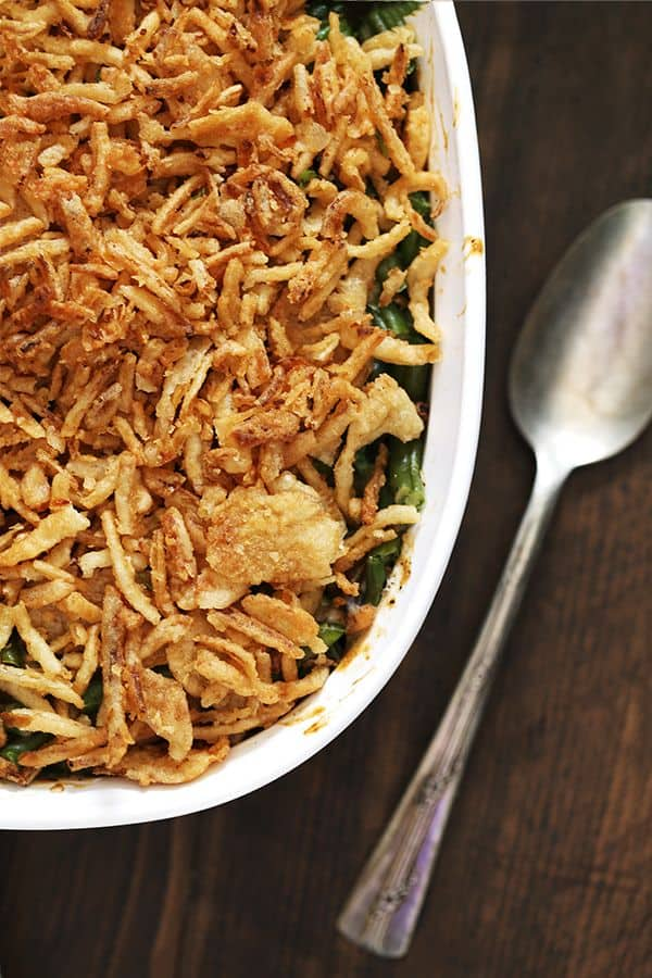 A white casserole dish of Twice the Onion Green Bean Casserole sits on a wooden surface with a spoon sitting to the right of it.