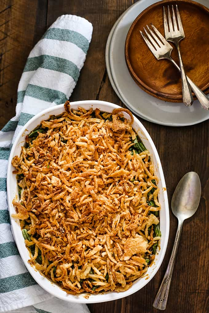 A white casserole dish of Twice the Onion Green Bean Casserole sits on a wooden surface surrounded by a striped napkin, spoon and a stack of white and wooden plates topped by two forks.