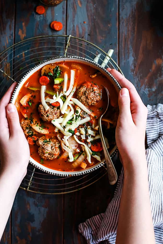 Two hands reach for a bowl of Meatball Pizza Soup.