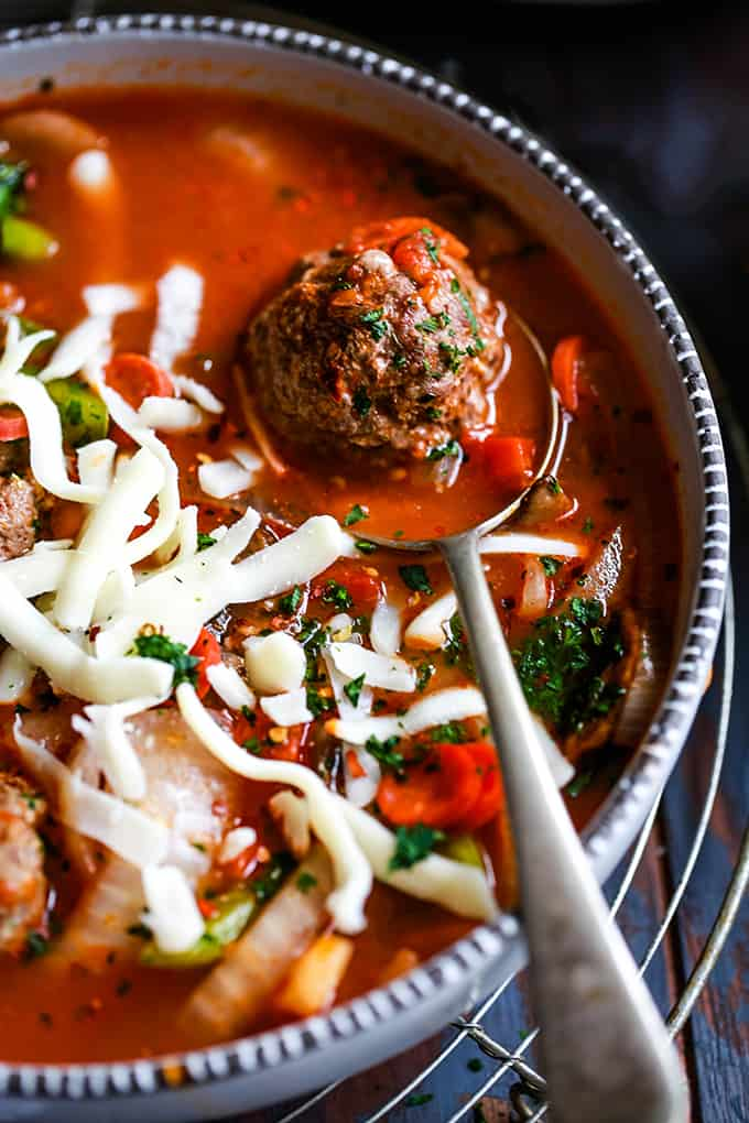A meatball rests on a spoon in the middle of a bowl of Meatball Pizza Soup.