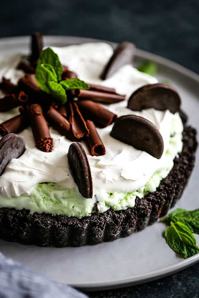 A Grasshopper Ice Cream Tart is garnished with mint cookies, chocolate curls and fresh mint.