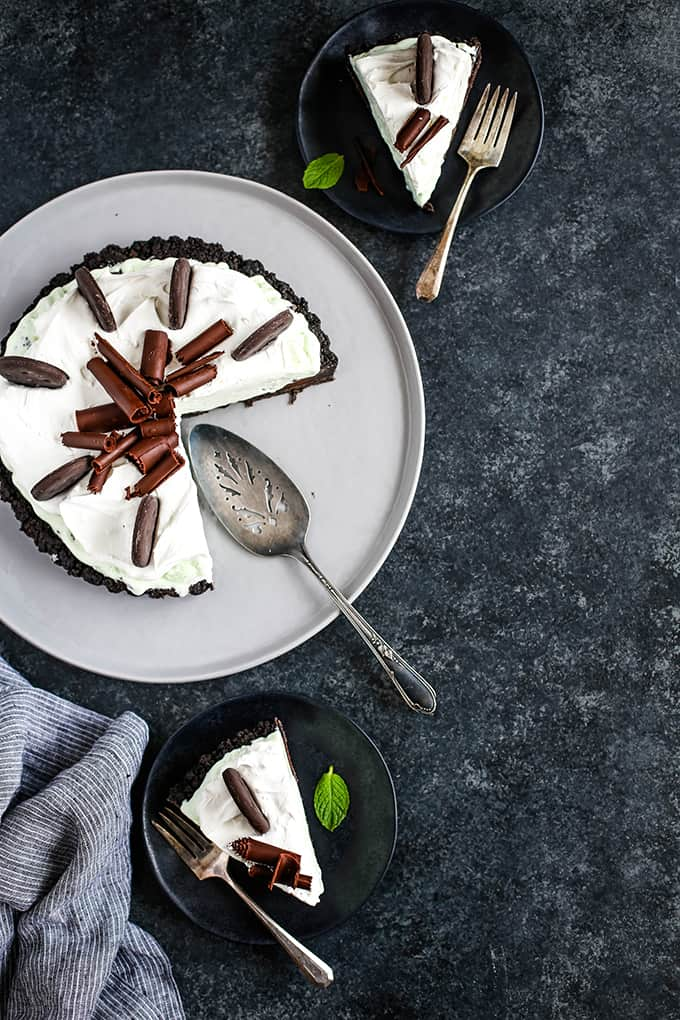 A Grasshopper Ice Cream Tart sits on a grey serving plate while two slices of tart rest on black plates with forks.