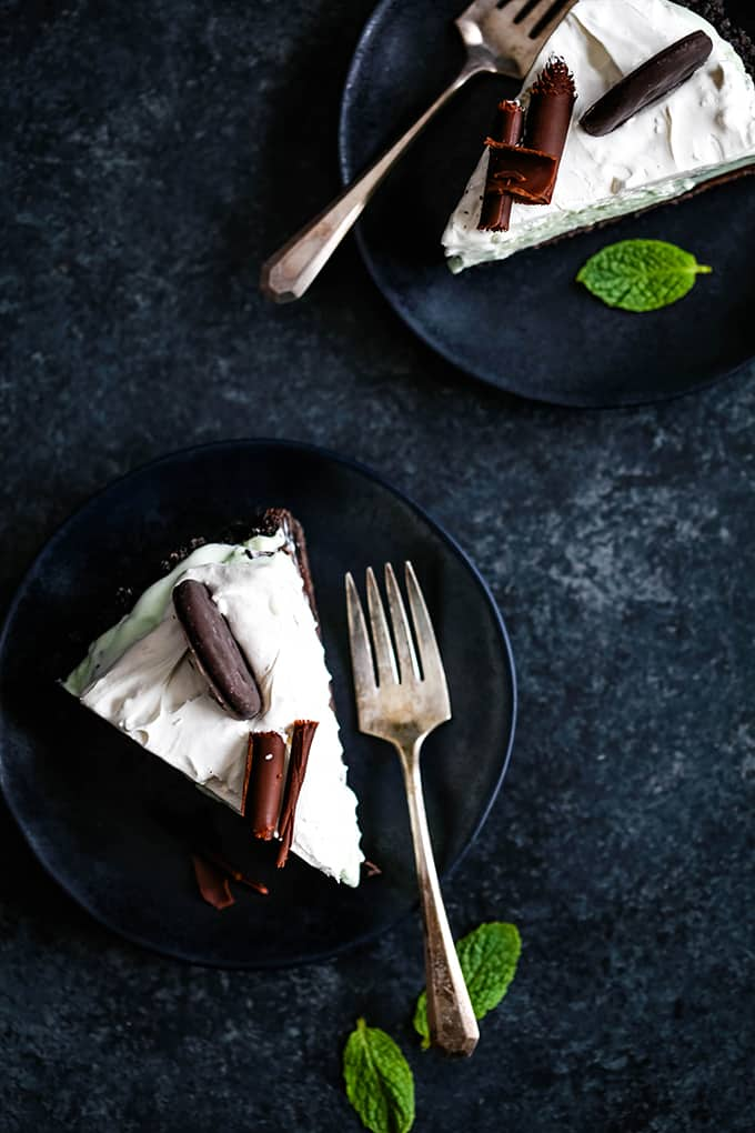 Two slices of Grasshopper Ice Cream tart sit on plates with forks and garnished with fresh mint leaves.