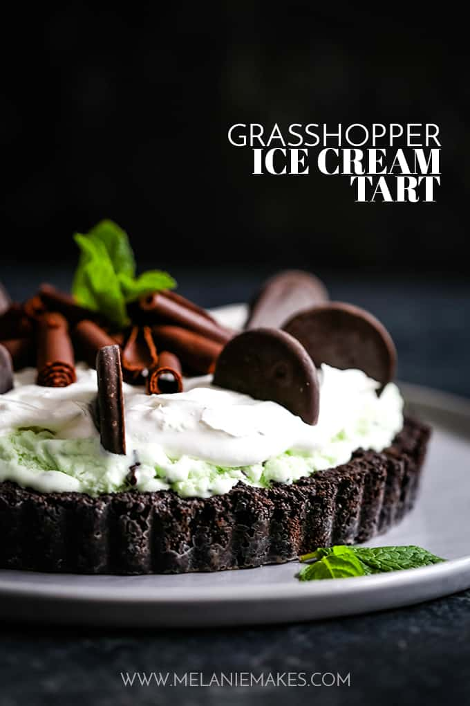 A Grasshopper Ice Cream Tart sits on a grey plate garnished by mint leaves.