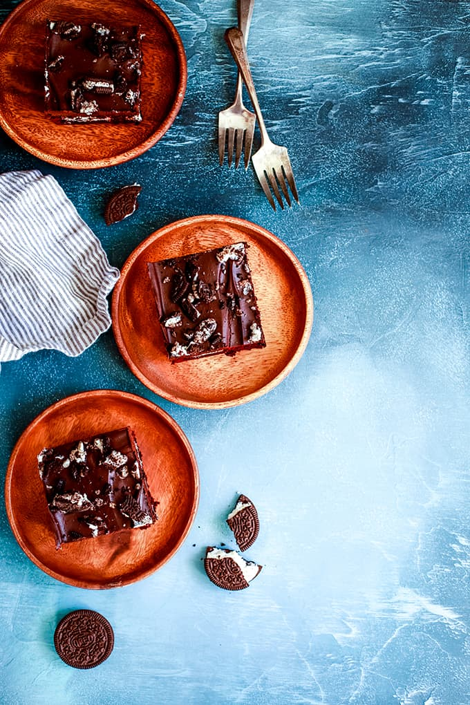 Three Oreo Stuffed Red Velvet Brownies sit on wooden plates with a striped napkin and forks.