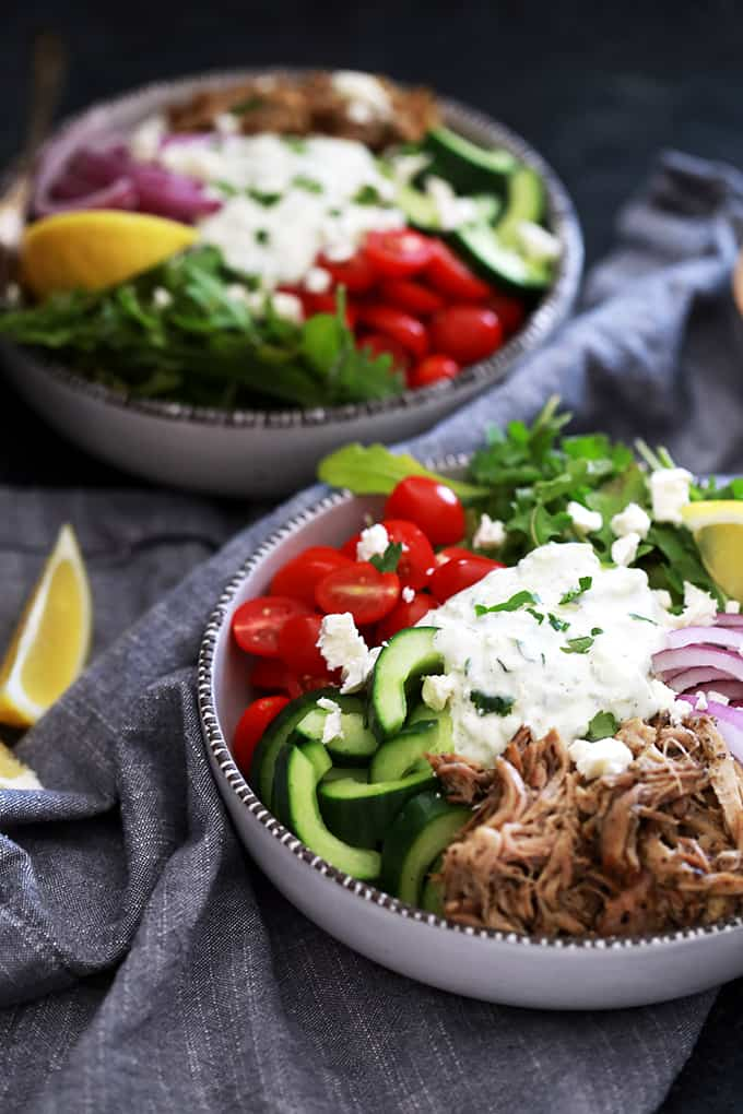 Minimal effort is required to create these delicious Slow Cooker Pulled Pork Gyro Bowls. Greek and herb infused pulled pork, tomatoes, cucumbers, arugula and red onion is topped with a dollop of tzatziki sauce and feta cheese before being showered with a squeeze of fresh lemon.