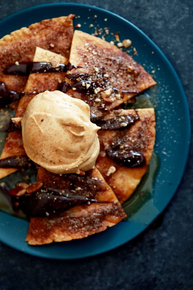 These Turtle Churro Nachos are the perfect dessert to feed a crowd. Homemade cinnamon and sugar speckled tortilla chips are drizzled with caramel sauce and chocolate ganache before being crowned with a dollop of caramel cream cheese. They're then sprinkled with chopped pecans and additional cinnamon sugar.
