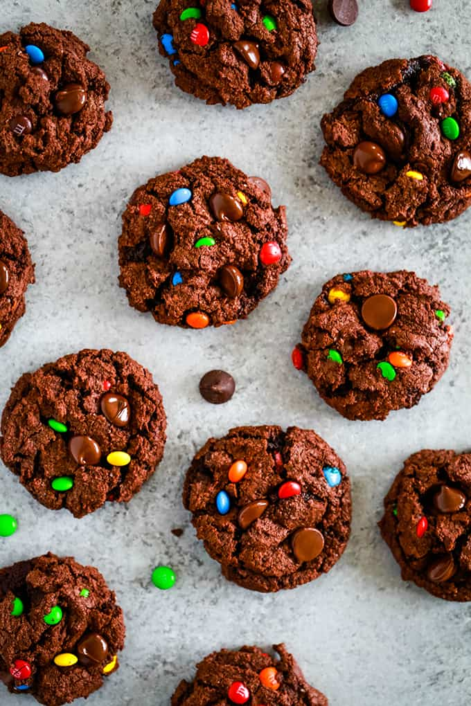 Double Chocolate M&M Cookies rest on a grey speckled surface.