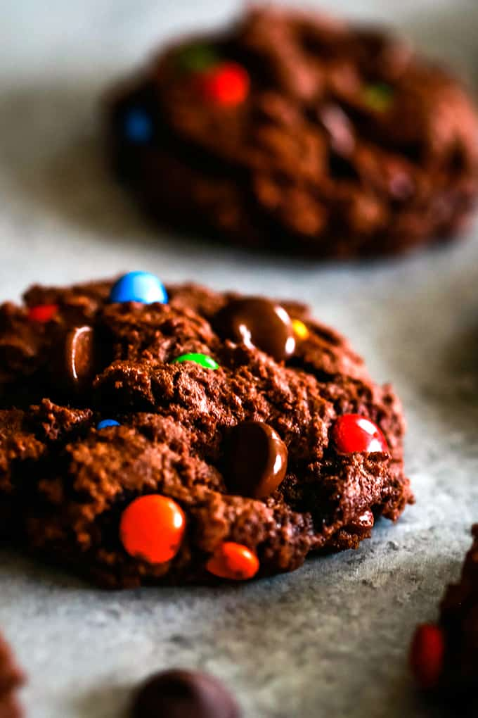 A Double Chocolate M&M Cookie sits on a surface in front of another cookie.
