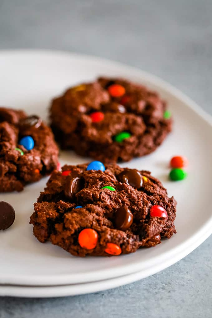 Three Double Chocolate M&M Cookies sit on a white plate.
