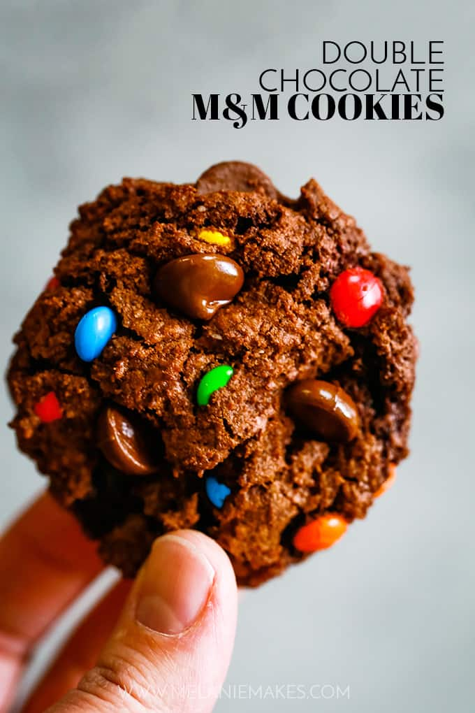 A hand holds a Double Chocolate M&M Cookie.
