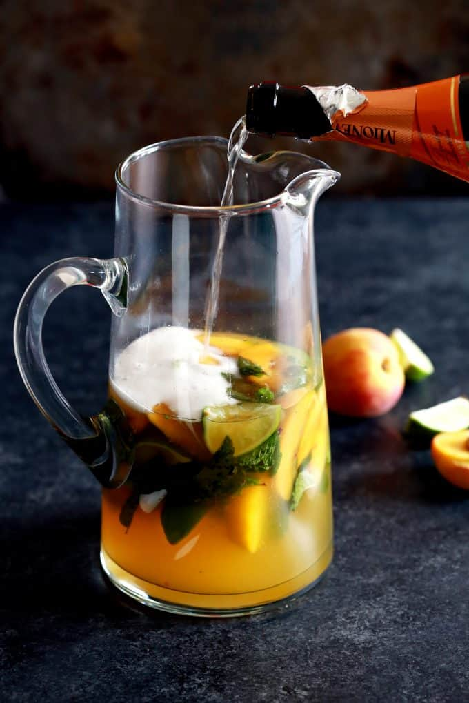 These seven ingredient Peach Prosecco Mojitos couldn't be easier. Fresh mint and limes are muddled together before being doused in peach juice, simple syrup, white rum and Prosecco. Served over ice and garnished with a peach wedge and additional mint, this is one refreshing cocktail.