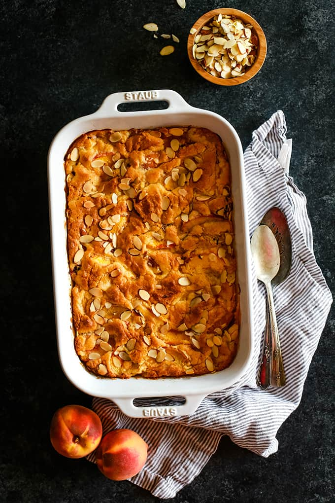 An overhead view of a Cake Mix Fresh Peach Cobbler flanked by a striped napkin, serving spoons, fresh peaches and a bowl of sliced almonds.