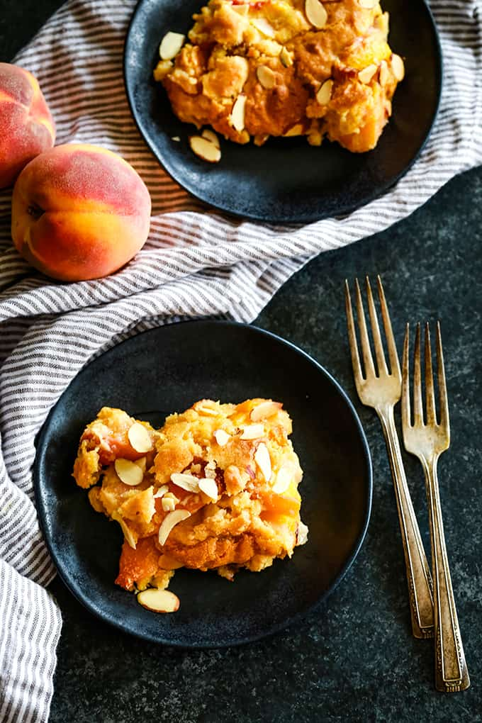 An overhead view of two plates of Cake Mix Fresh Peach Cobbler flanked by a striped napkin, fresh peaches and forks.