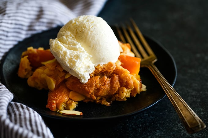 A serving of Cake Mix Fresh Peach Cobbler on a black plate with a fork.