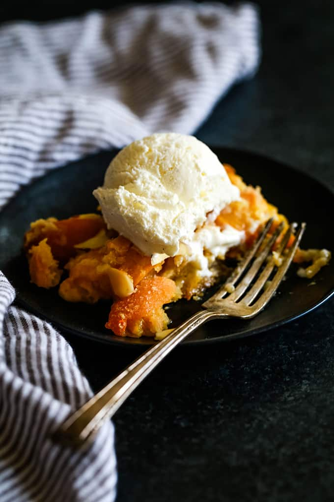 Cake Mix Fresh Peach Cobbler served on a black plate and topped with a scoop of vanilla ice cream.  A bite is removed and a fork rests on the plate.