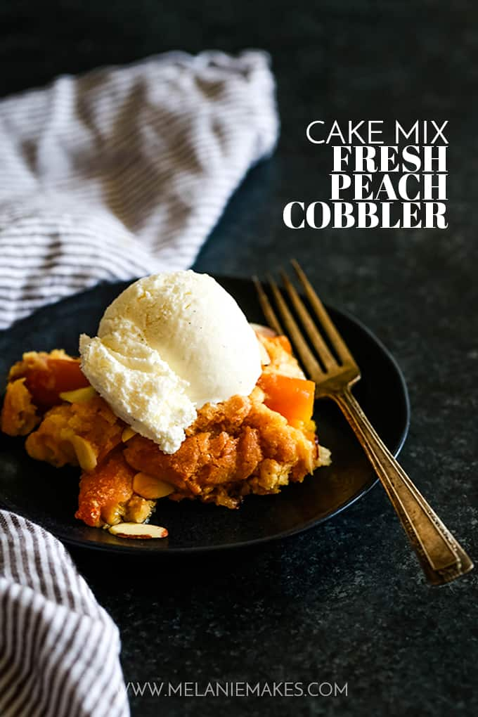 A serving of Cake Mix Fresh Peach Cobbler topped with a scoop of vanilla ice cream on a black plate with a fork.