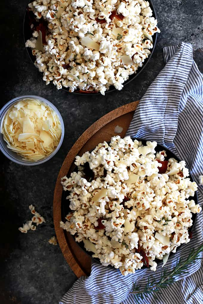 I've combined three of my favorite ingredients to make this Rosemary Parmesan Bacon Popcorn truly legendary.  Kernels of popcorn take a swim in bacon fat before popping and then tossed with fresh rosemary, shaved Parmesan cheese and crumbled bacon.  Perfect for movie night, game day or any time you need an amazing savory snack.