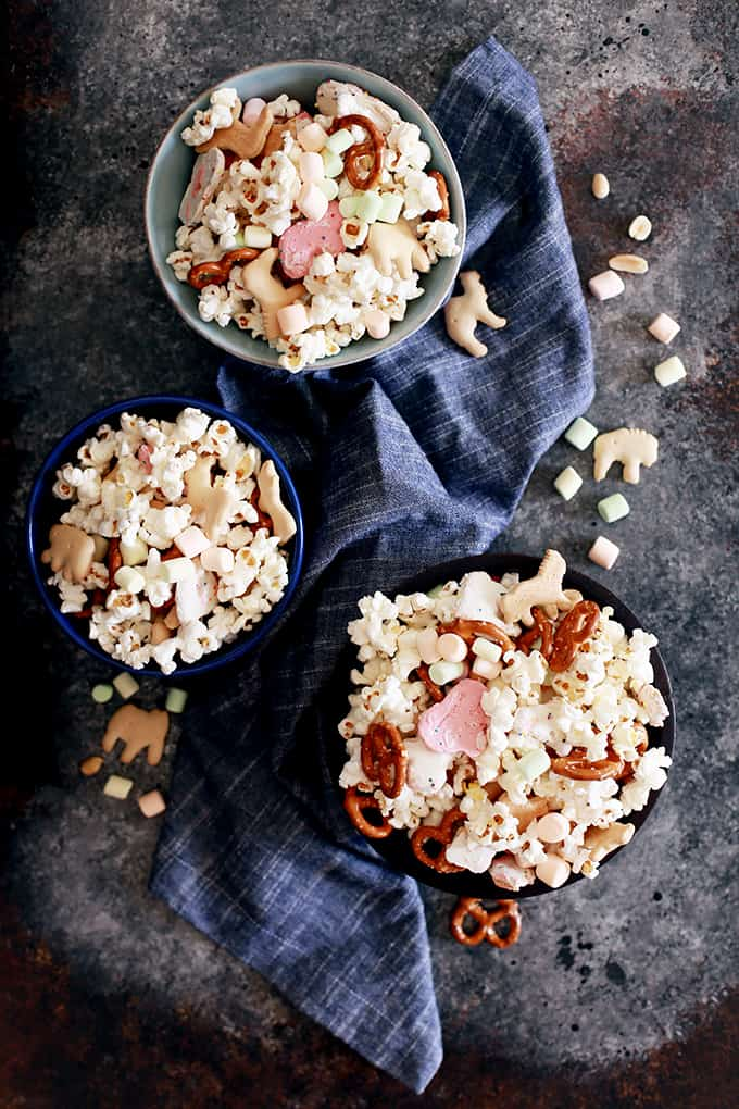This Animal Cookie Snack Mix is popular with young and old alike.  Freshly popped popcorn is tossed with animal crackers, frosted animal cookies, miniature fruit marshmallows, mini pretzels and peanuts for the perfect sweet and savory snack mix.