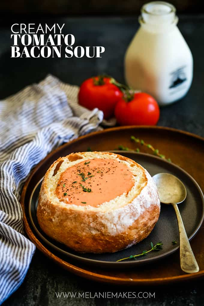 Creamy Tomato Bacon Soup in a bread bowl on a dark plate and wood platter.