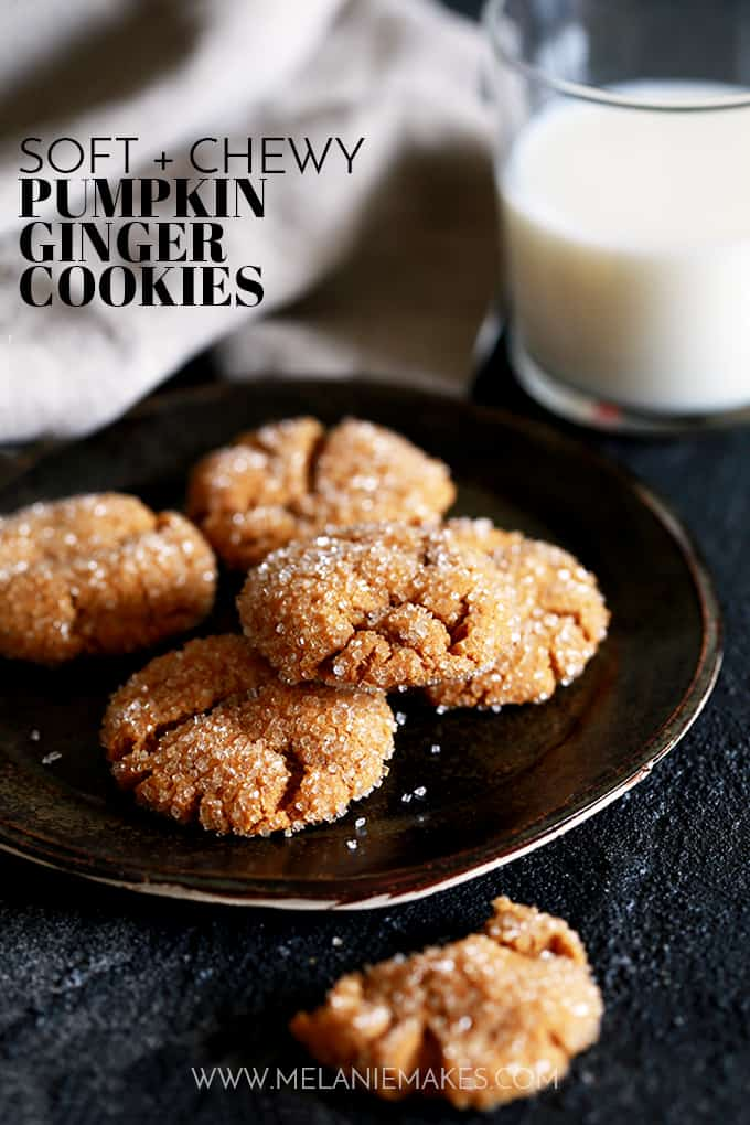 A plate of Soft and Chewy Pumpkin Ginger Cookies sit on a dark background with a glass of milk and a napkin in the background. One cookie is in front of the plate.