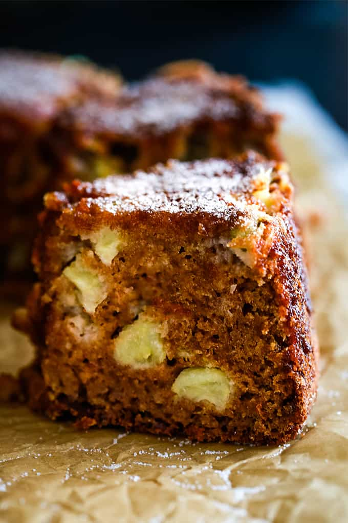 A slice of Cinnamon Sugar Apple Cake on brown parchment paper.