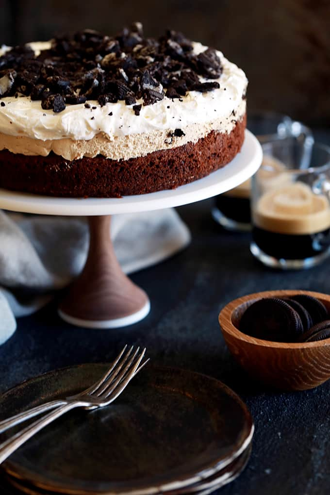 This Coffee Cookies and Cream Cheesecake Brownie Cake is like enjoying five of your favorite desserts all at once. A brownie base is topped with a mocha infused cheesecake studded with Oreos before being topped by a cloud of whipped topping and even more crushed cookies. Basically each and every bite is like pure and absolute heaven.