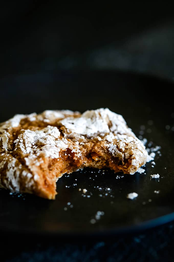 A Caramel Pumpkin Spice Crinkle Cookie with a bite removed sitting on a black plate.