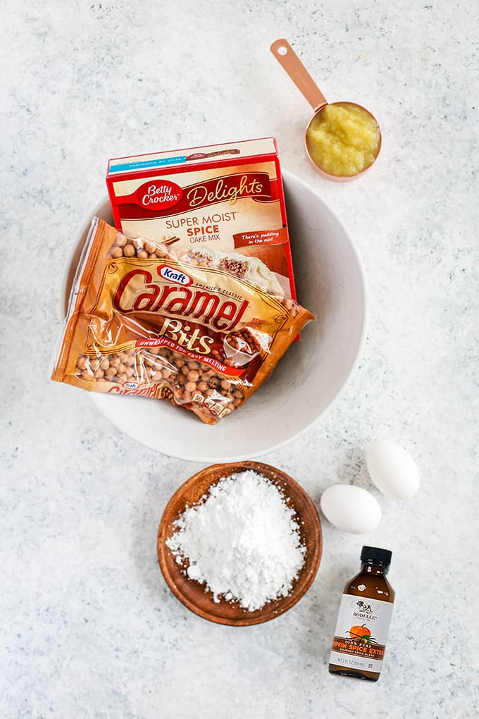 All of the needed ingredients for Caramel Pumpkin Spice Crinkle Cookies on a white speckled background.