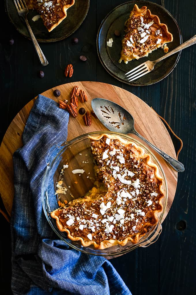 An overhead shot of a Chocolate Pecan Coconut Custard Pie on a wooden platter surrounded by a blue napkin, pie server, pecans, chocolate chips and two plates with pieces of pie and forks.