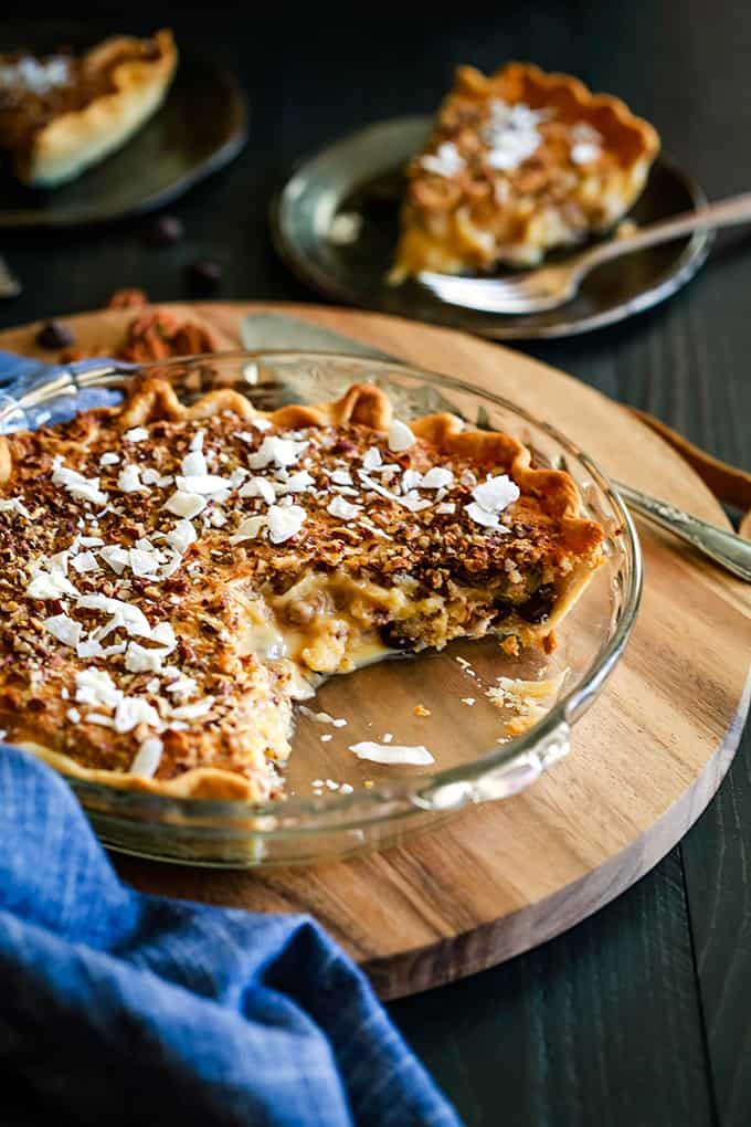 A Chocolate Pecan Coconut Custard Pie sits on a wooden platter surrounded by a blue napkin and two plates also with pieces of pie and forks.
