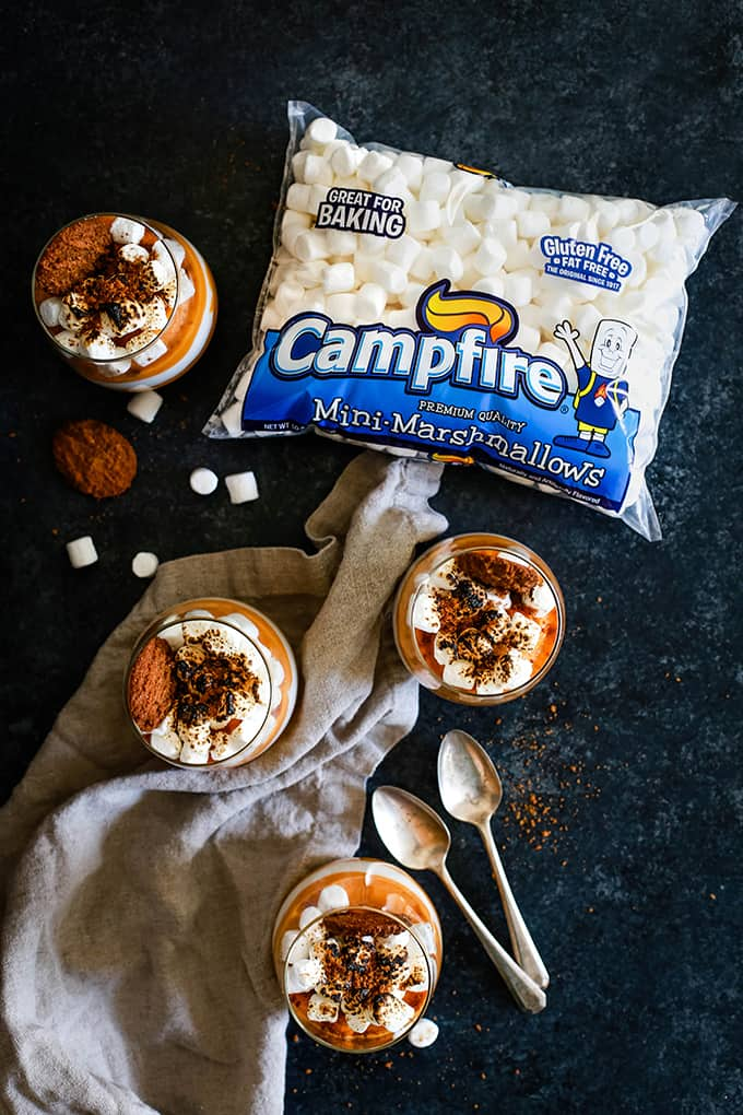 An overhead shot of four Gingersnap Sweet Potato Mousse desserts surrounded by a two spoons, a bag of Campfire Mini Marshmallows and a neutral colored napkin.
