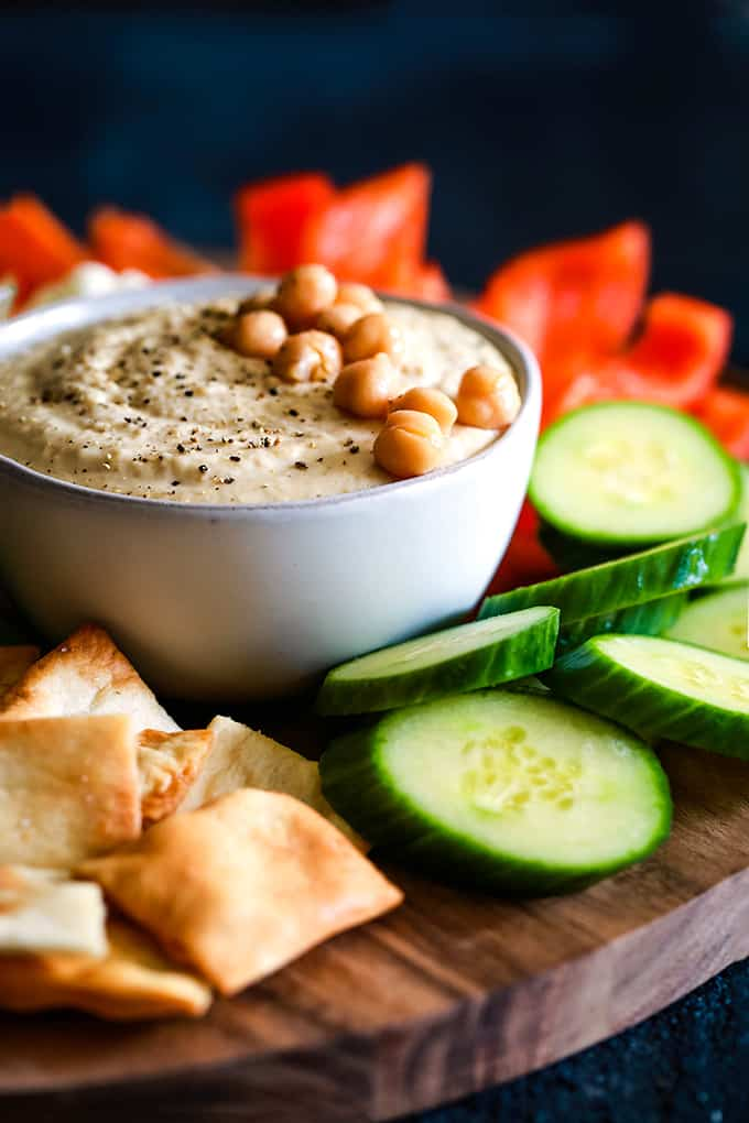A bowl of Horseradish hummus garnished with chickpeas on a wooden platter with vegetables and pita chips.