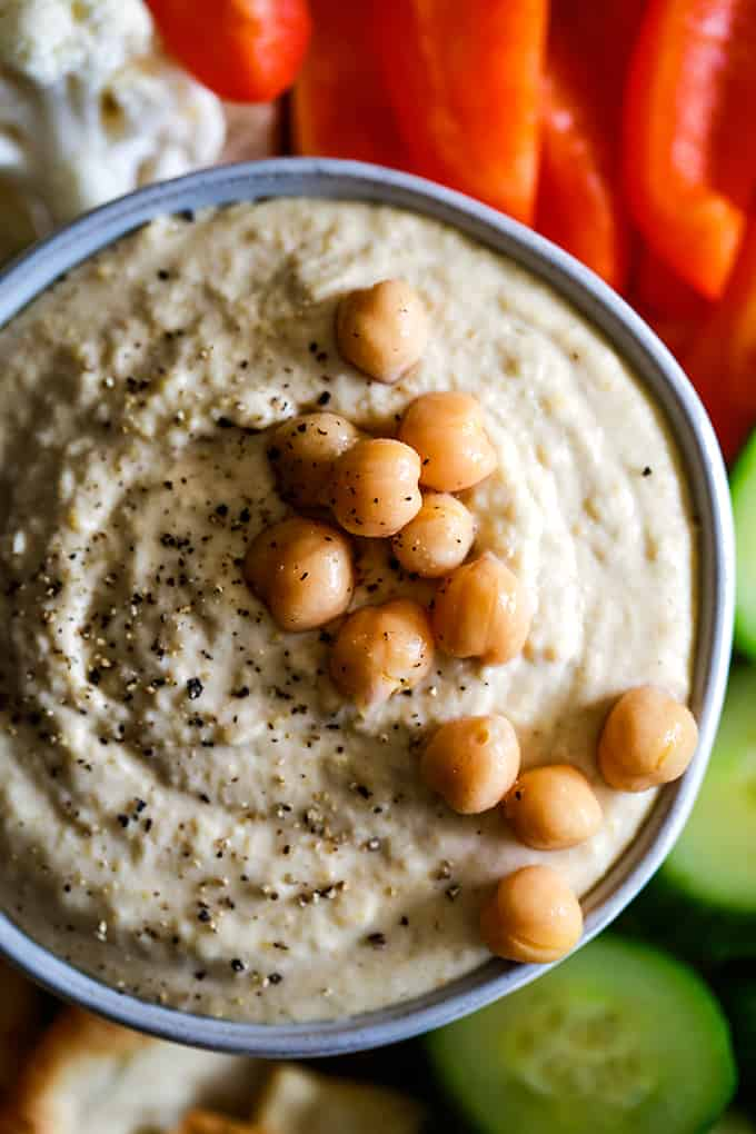 A bowl of Horseradish Hummus garnished with chickpeas and ground pepper.