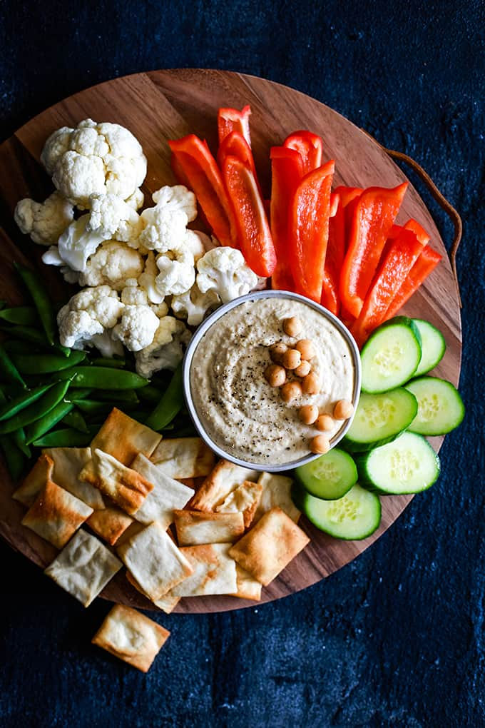 A wooden platter with a bowl of Horseradish Hummus surrounded by vegetables and pita chips.