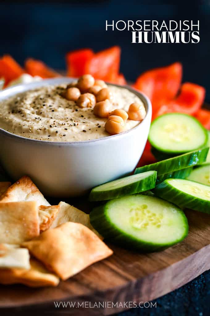 A bowl of Horseradish Hummus surrounded by vegetables and pita chips.