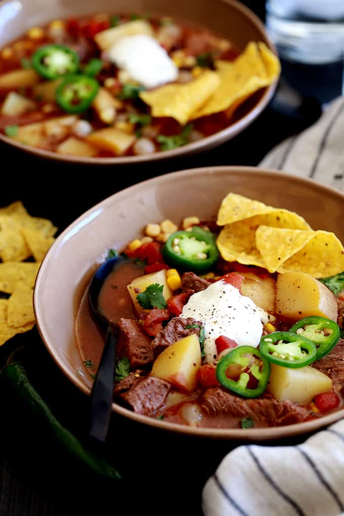 This Slow Cooker Mexican Beef Stew one of those slow cooker recipes where everything is simply poured into the slow cooker, the lid goes on, you hit the start button and forget about it.  Each bowl is then topped with slices of fresh jalapeño, sour cream, pico de gallo and tortilla chips.  An easy dinner idea for any night of the week!
