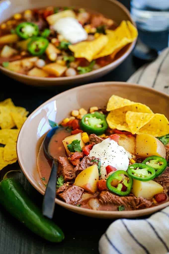 Two bowls of Slow Cooker Mexican Beef Stew sit on a dark background surrounded by a striped napkin, yellow tortilla chips and a jalapeño.